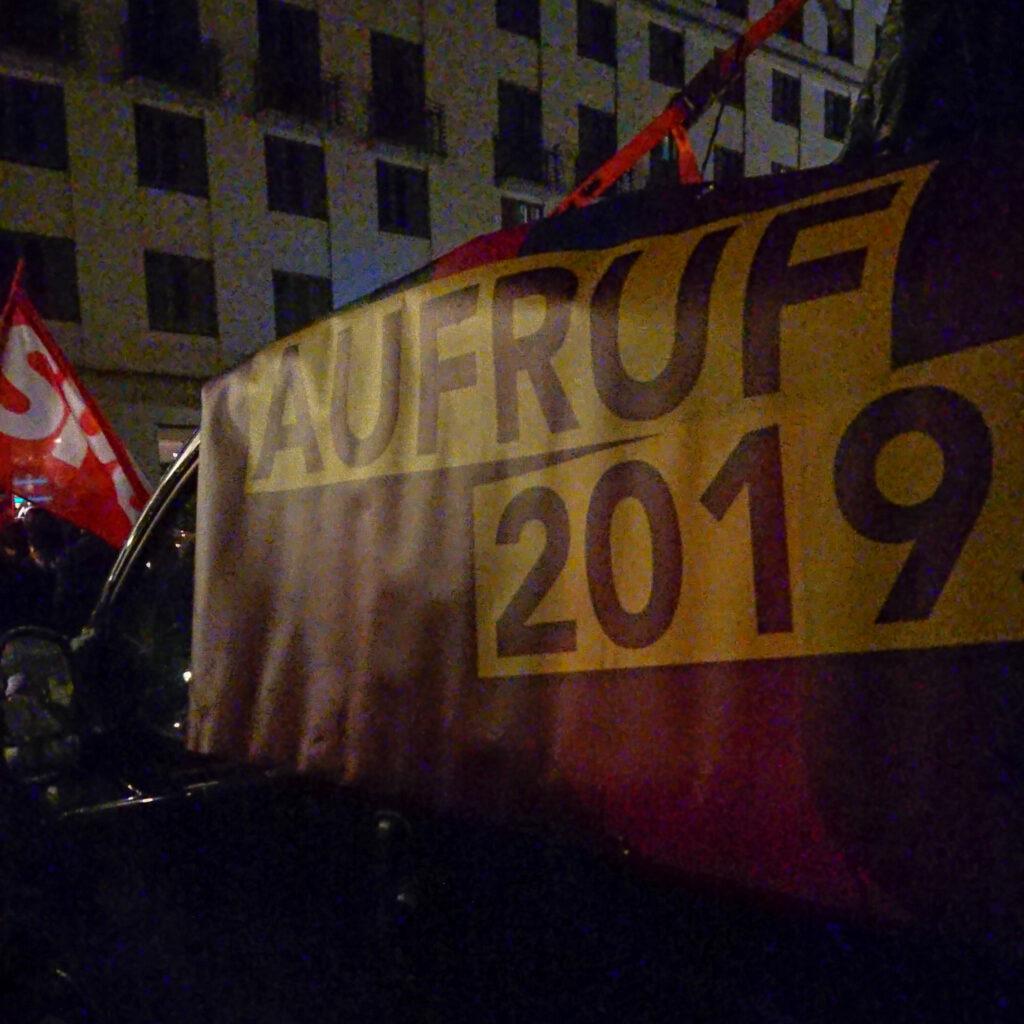 """Eine SPD-Fahne neben dem """"Aufruf 2019""""-Transparent"""