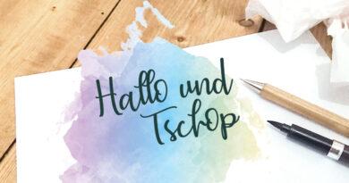 Symbolbild: Hallo und Tschop auf Papier mit Stiften