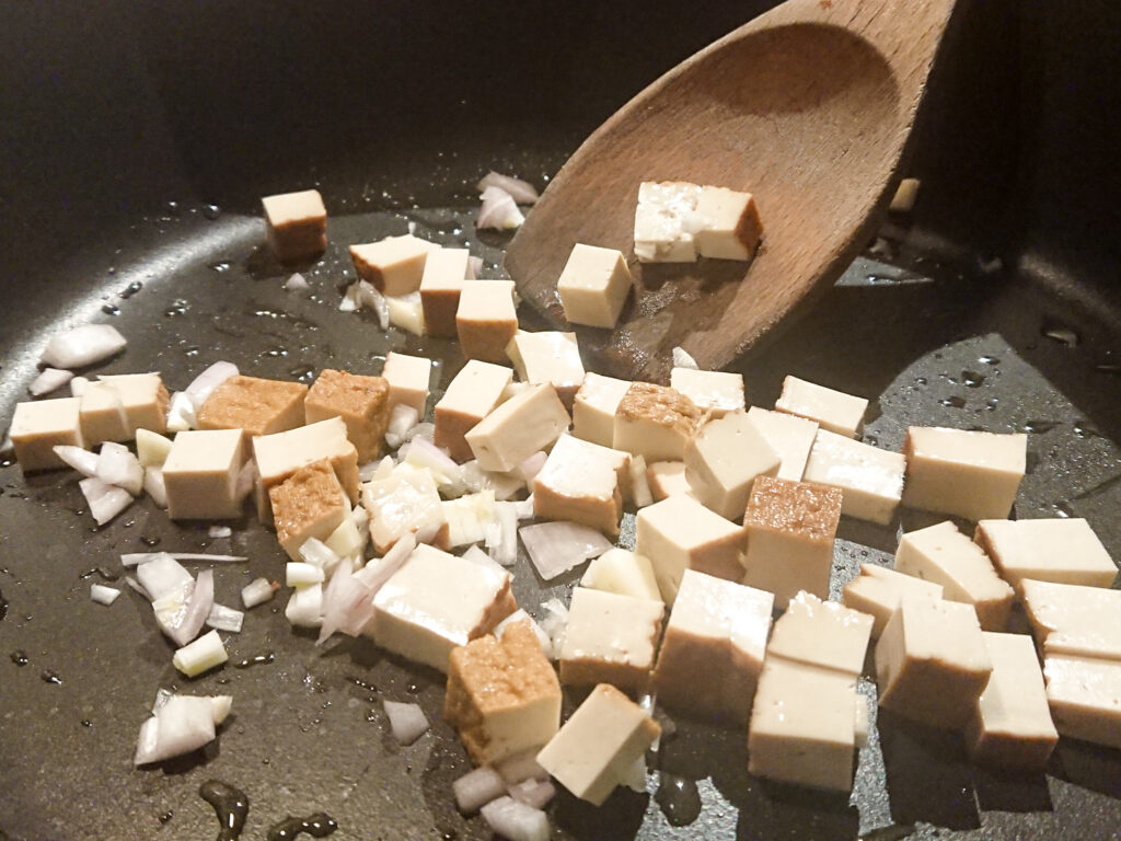 Die Tofuwürfel werden zusammen mit Zwiebeln und Knoblauch angebraten