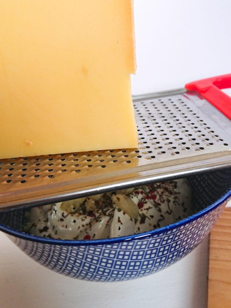Der Käse für den Knoblauchkäse Brotaufstrich wird gerieben