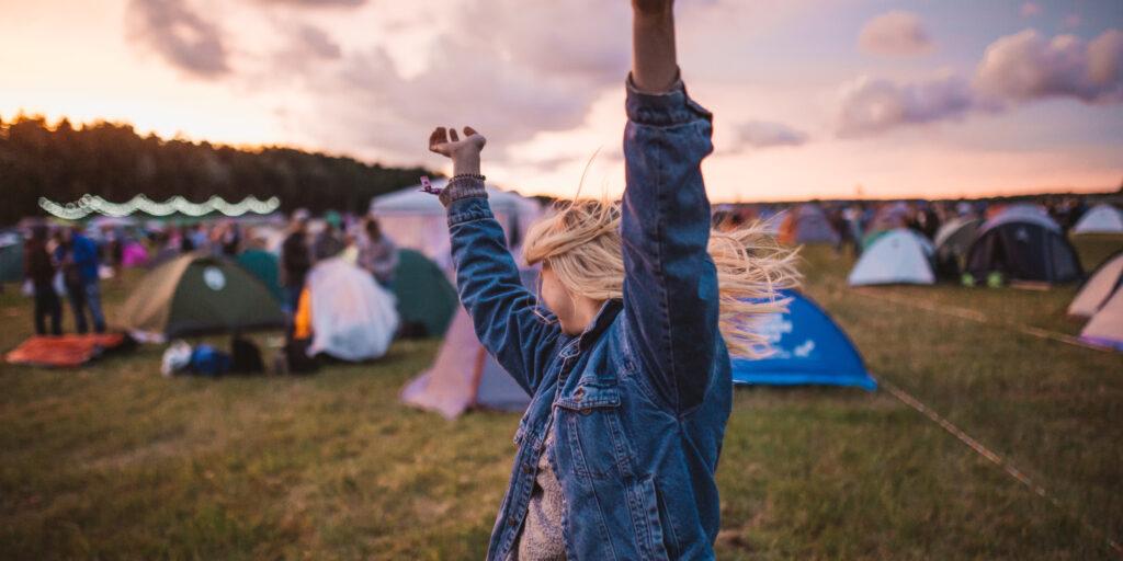 Eine Frau tanzt zwischen Zelten