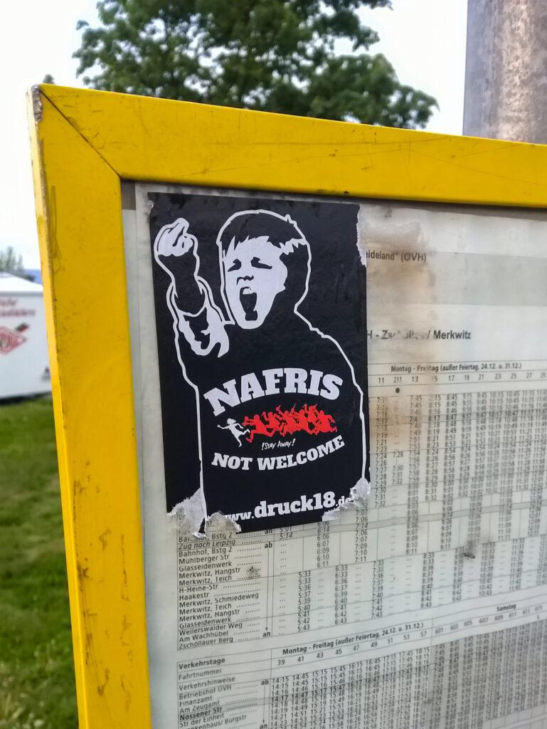 """Ein """"Nafris not Welcome"""" Sticker klebt an einem Haltestellenaushang"""