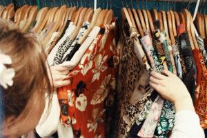 Kleidertauschparty: Eine Person schaut Kleidungsstücke auf Bügeln an