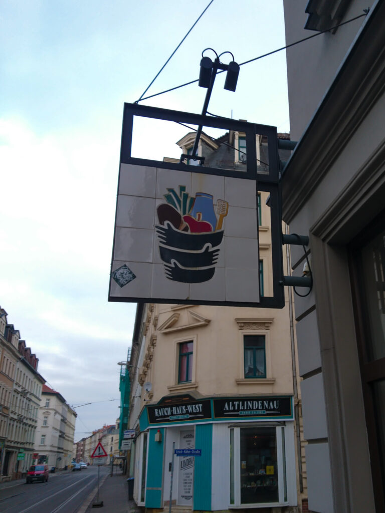 Schild mit Logo der Schwarzwurzel an der Tür des Laden.
