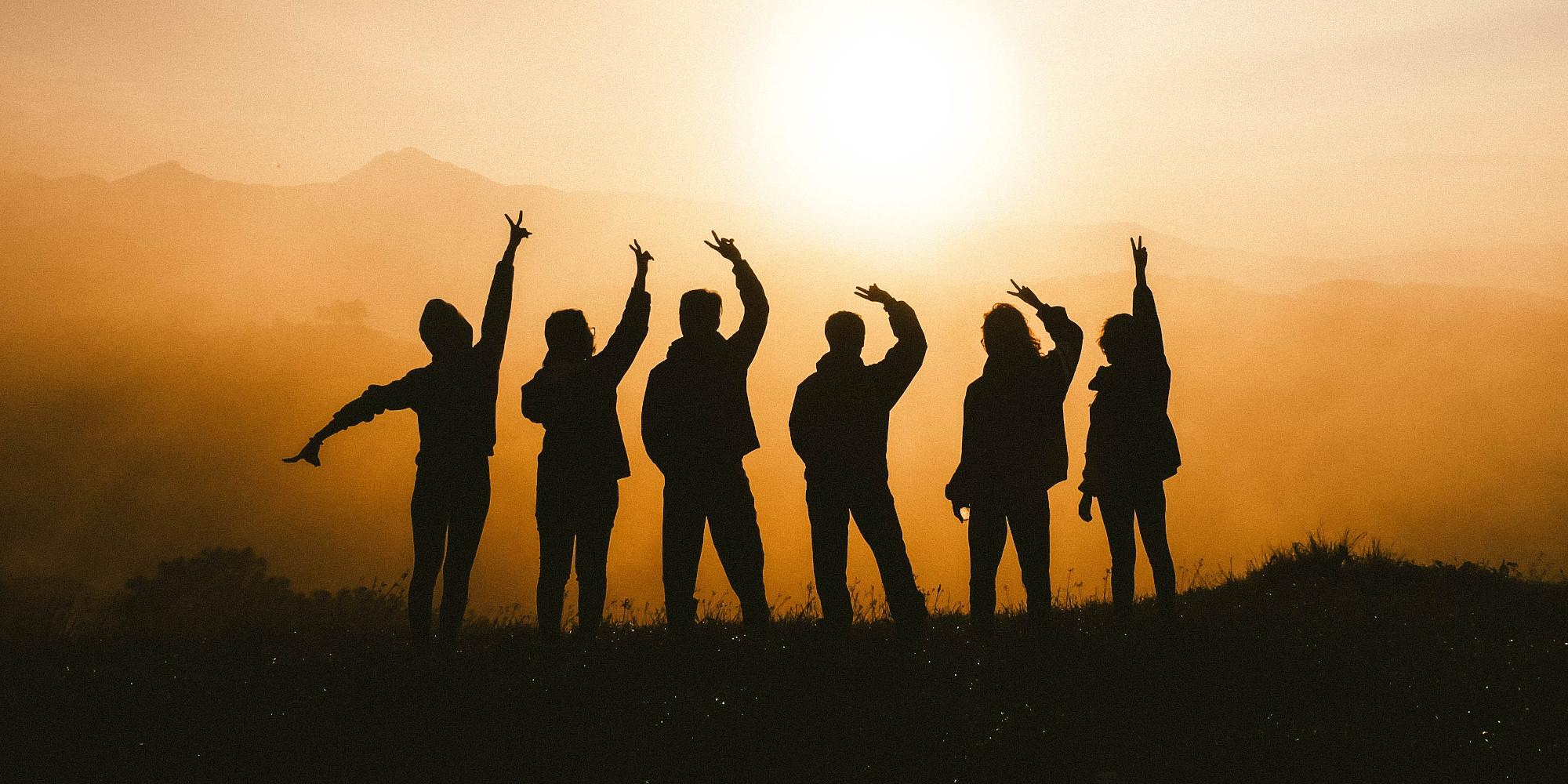 Start with a friend! - Sechs Personen stehen mit erhobenen Armen vorm Sonnenuntergang