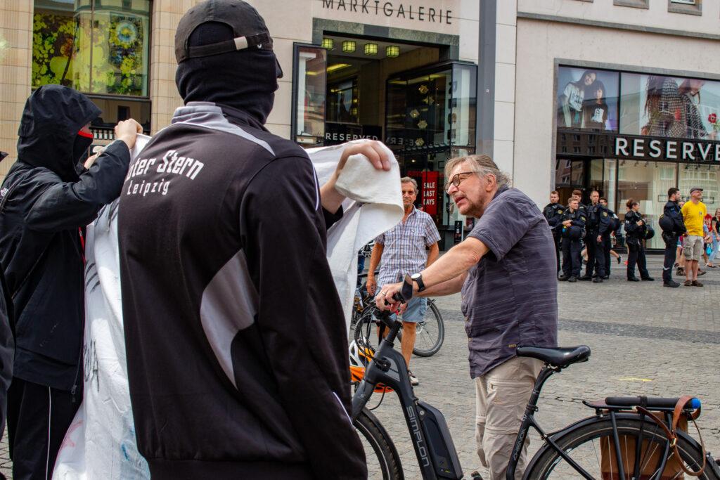Zwei Personen protestieren mit Transparent in der Hand. Ein Mann auf einem Fahrrad und ohne Maske spricht sie an.