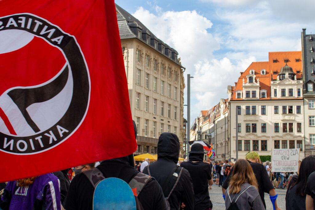 """Antifaschist*innen protestieren auf dem Leipziger Marktplatz gegen die """"Bewegung Leipzig"""", bei der eine Reichsflagge weht"""