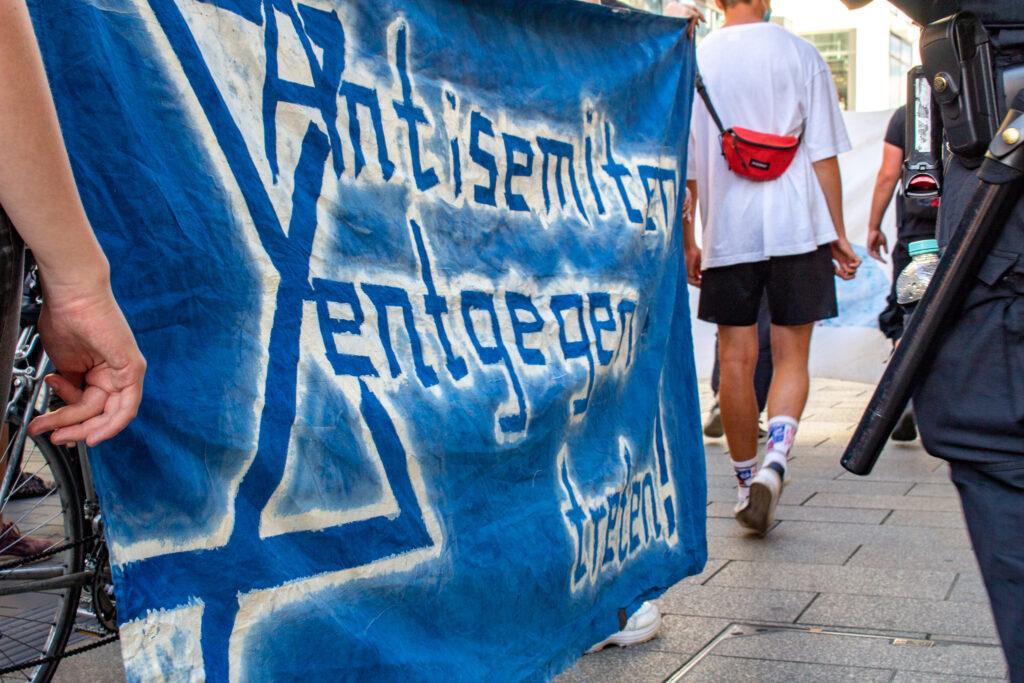 """Der Protest trägt ein Transparent mit der Aufschrift """"Antisemiten entgegentreten"""""""