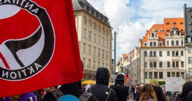 """Antifaschistischer Protest steht auf dem Marktplatz in Leipzig, im Hintergrund ist die Demo der """"Bewegung Leipzig"""" zu sehen, bei der eine Reichsflagge weht"""