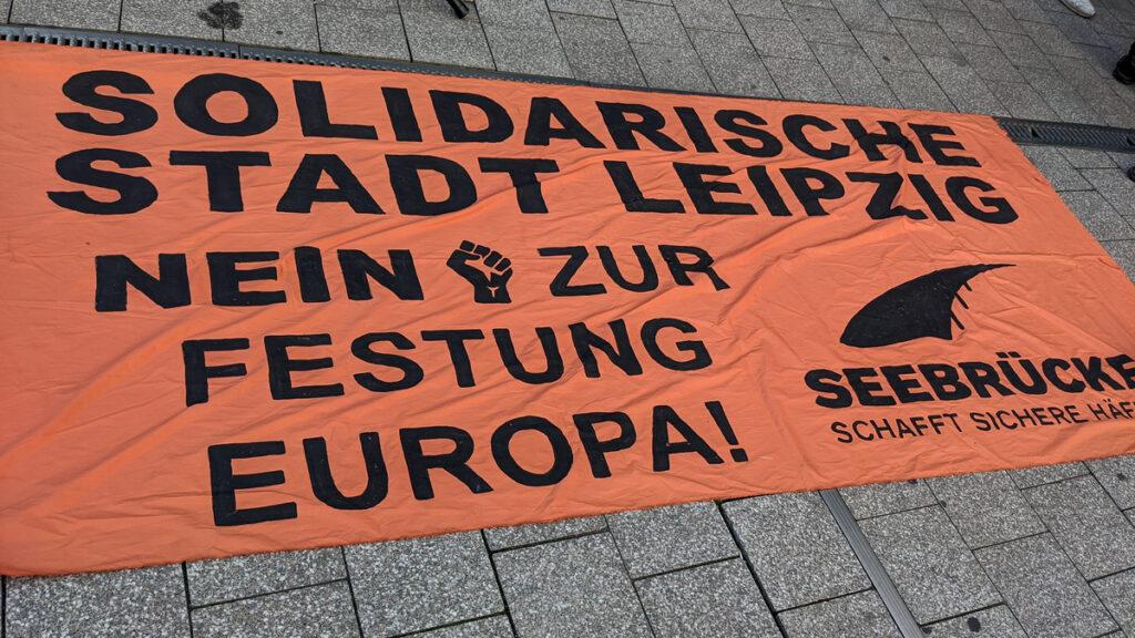 """Foto: Transpent auf dem Boden """"Solidarische Stadt Leipzig Nein zur Festung Europa"""" - Seebrücke schafft Sichere Häfen"""
